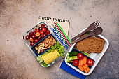 Back to school concept. Lunch box with healthy fresh food. Sandwich, vegetables, fruits and nuts in food containers, dark background.