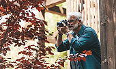A mature man with a beard and a camera takes pictures, paparazzi. Retired active hobby, senior journalist