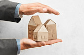 Hand holds house. Buying or selling home, real estate insurance. Protection and safety life