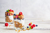 Yogurt parfait with granola, raspberries, honey and blueberries in glasses, light gray background, copy space. Healthy breakfast concept.