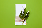 Congratulation and invitation to the holiday. Lily of the valley flowers and a note on a green background