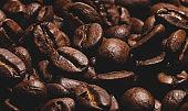 Brown roasted beans of arabica coffee. Dark background