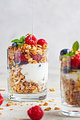 Yogurt parfait with granola, raspberries and blueberries in glasses, light gray background, vertical. Healthy breakfast concept.