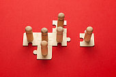 Wooden figures on puzzles on red background as a symbol of team building. Organization group people in business. Cooperation and partnership