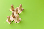 Wooden figures on puzzles on green background as a symbol of team building. Organization group people in business. Cooperation and partnership