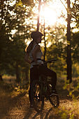 Silhouette of a woman biker in the forest in the rays of the sunset. Training in nature, escape from the city
