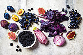 Raw purple vegetables and fruits on gray concrete background. Flat lay of purple food. Eggplant, grapes, figs, plums, blackberries, onions and basil, top view.