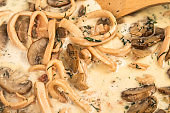 Cooking creamy sauce with squid and mushrooms. Close-up