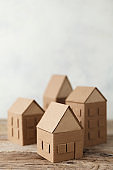 Cardboard toy houses on wooden background. Sale or rental of housing. Neighbors in house. Comfortable life in suburbs