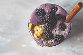 Berry smoothie with peanut butter and hemp seeds in glass, top view. Healthy vegan food concept.