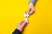 Two hands connect puzzles on a yellow background. Cooperation and teamwork in business. Collaboration people for success