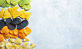 Different types of colored potato chips, gray background, copy space. Fast food concept.