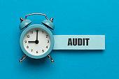 Time for audit, concept. Finance clock on blue background