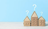 A question on a small house, a magnifying glass examines the building. Assistance in choosing and buying real estate