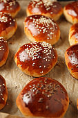 Fresh hot sweet buns with sesame seeds from the oven, homemade bakery