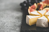 Sliced brie or camembert cheese with figs and grapes