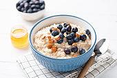 Oatmeal porridge bowl with blueberries, almonds, honey