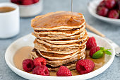 Syrup pouring on stack of whole wheat pancakes