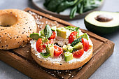 Bagel with cream cheese, avocado and tomatoes