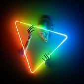 3d render, abstract modern minimal concept. Mannequin body parts, bald head, woman face, hands holding triangle. Portrait inside colorful neon glowing light triangular frame