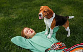 Happy woman and Beagle dog enjoying time together in park