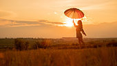 Inspiring female with umbrella against sunset sky