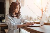 Female freelancer using laptop in cafe