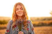 Happy young woman with flowers in field