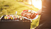 Crop chef with roasted meat and vegetables near grill
