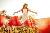 Relaxed positive woman spreading hands walking on flower field