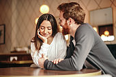 Multiethnic loving couple flirting in coffee shop