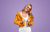 Joyful millennial woman in trendy outfit on lilac background