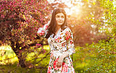 Graceful woman with charming smile in garden among flowering tree