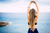 Healthy lifestyle people concept with beautiful long blonde hair girl viewed from back do some stretching in front of the ocean view outdoor - fit woman and attractive female