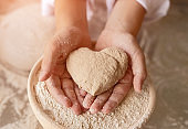 Heart shaped dough for bread cooked by mother and child