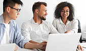 Cheerful multiracial colleagues using laptop in office together