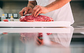 Hands Of A Chef Cutting Big Piece Of Meat With His Reflection On The Kitchen  Table
