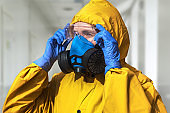 Virologist in a protective yellow suit and a respirator in the hospital. The doctor is wearing goggles, gloves, and a mask.