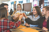 Group of people hanging out with each other in a bar and enjoying their company - Friends cheering with beer and having fun , smiling , quality time in friendship relation - Lifestyle concept