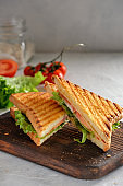 Cheese sandwich of toasted bread with a crispy crust with fresh tomatoes and herbs on a wooden board