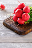 Healthy and wholesome food. Fresh radish with green leaves on a wooden table