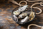 Lots of oysters in a black metal basket on a brown wooden table. Rustic style. French cuisine