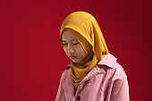 Portrait of sad young Asian teenage muslim girl wearing hijab looking down and depressed