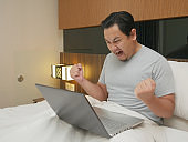 Portrait of young Asian man celebrating victory while looking at laptop on his bed, winning gesture with big smile