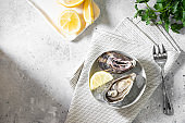 Oysters in a gray bowl with ice on a light gray table. Healthy seafood
