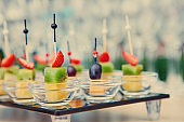 buffet at the wedding Banquet.  Glasses of wine and champagne. Assortment of fruit canapes on a glass Board. Banquet service. food, snacks with cheese, jamon, prosciutto and fruit