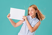 A beautiful smiling teenage girl holds a white banner and looks at it while standing on a turquoise background. Space for text, message, ad, or logo