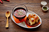 Traditional Ukrainian Russian vegetable borscht on an old wooden background in portioned cast iron. With herbs, sour cream and garlic bread.