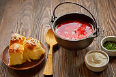 Traditional Ukrainian Russian vegetable borscht on an old wooden background in portioned cast iron. With herbs, sour cream and garlic bread