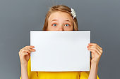 A teenage girl in yellow clothes on a grey background holds a blank white poster for the concept insert